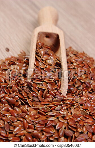 Heap of linseed with spoon on wooden background - csp30546087