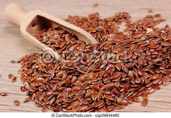 Heap of linseed with spoon on wooden background - csp39644480