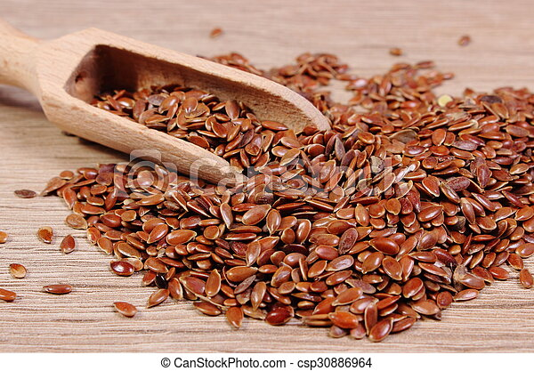 Heap of linseed with spoon on wooden background - csp30886964