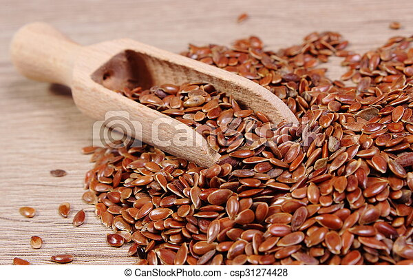 Heap of linseed with spoon on wooden background - csp31274428