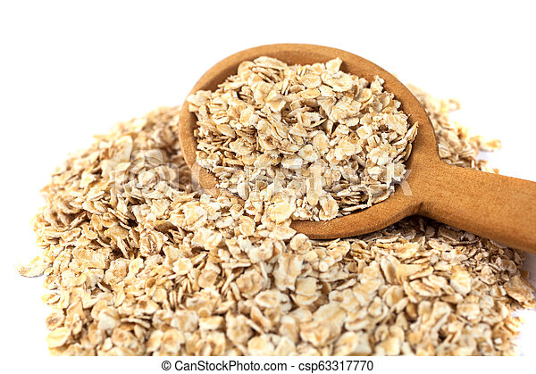 Heap of rolled oats with wooden spoon on white - csp63317770