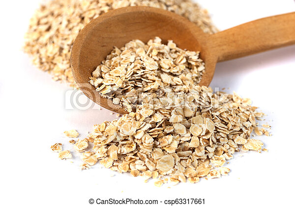 Heap of rolled oats with wooden spoon on white - csp63317661