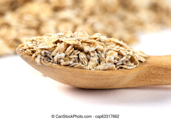 Heap of rolled oats with wooden spoon on white - csp63317662