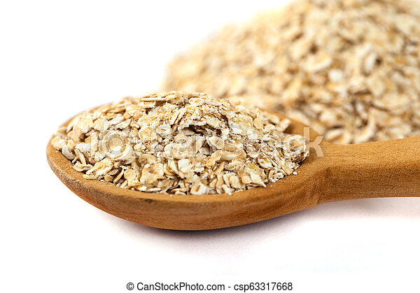 Heap of rolled oats with wooden spoon on white - csp63317668