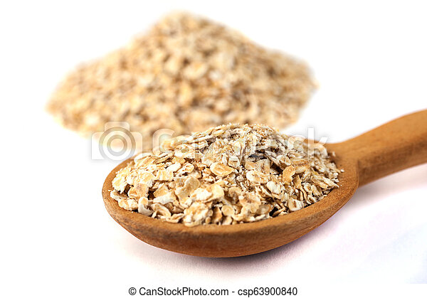 Heap of rolled oats with wooden spoon on white - csp63900840