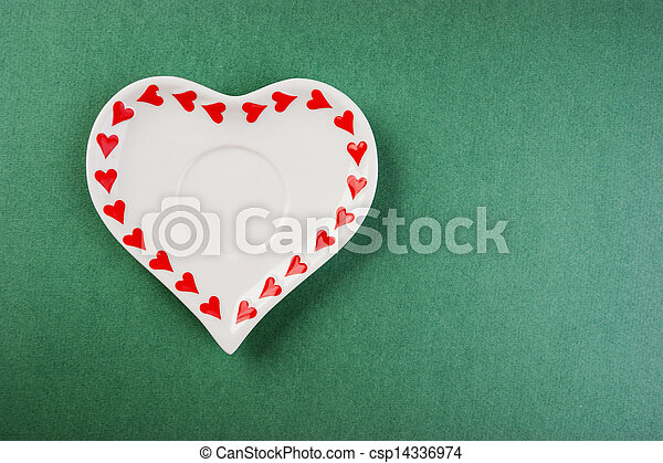 Heart form white plate on a green background - csp14336974