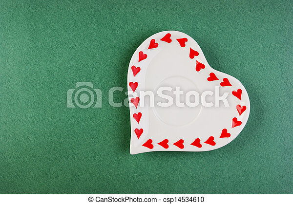 Heart form white plate on a green background - csp14534610