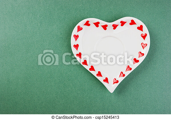 Heart form white plate on a green background - csp15245413