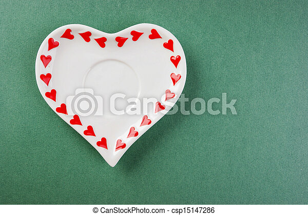 Heart form white plate on a green background - csp15147286