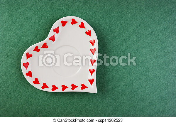 Heart form white plate on a green background - csp14202523