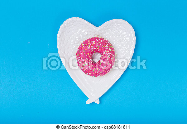 Heart form white plate on blue background - csp68181811