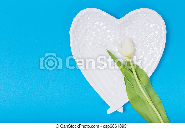 Heart form white plate on blue background - csp68618931