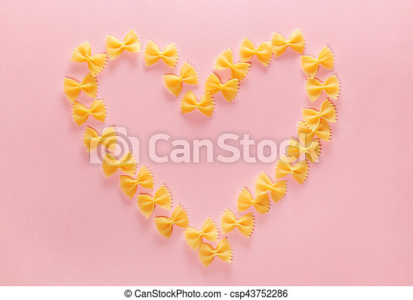 Heart frame from wheat pasta farfalle on rose background. Valentine's day. - csp43752286
