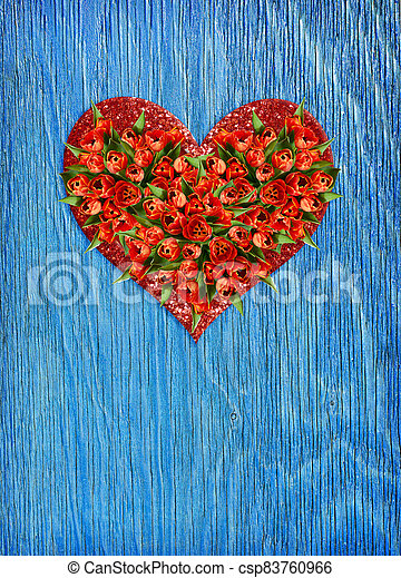 Heart shape bouquet of red tulip flowers in a glitter heart on blue wood - csp83760966