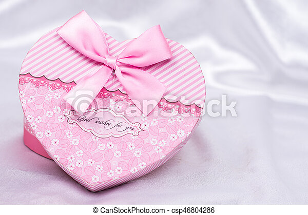 Heart shaped gift box with bow over white satin - csp46804286