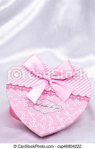 Heart shaped gift box with bow over white satin - csp46804222