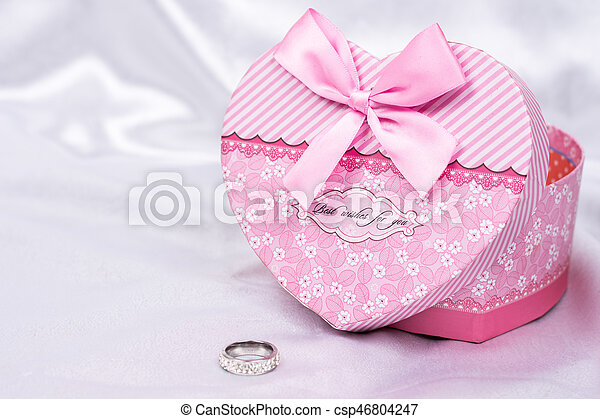 Heart shaped gift box with wedding ring over white satin - csp46804247