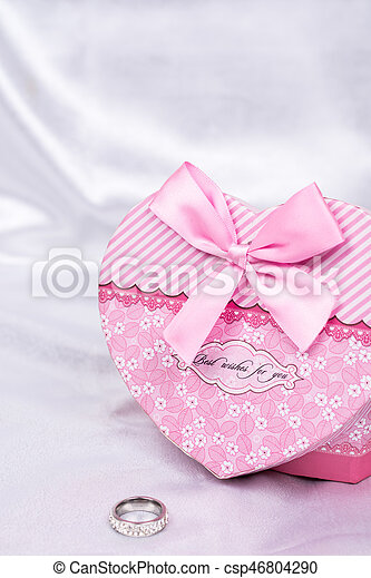 Heart shaped gift box with wedding ring over white satin - csp46804290