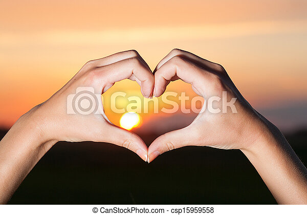 Heart shaped hands with sunrise.