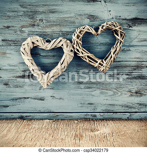 two heart shaped ornaments made with natural fibers against a blue