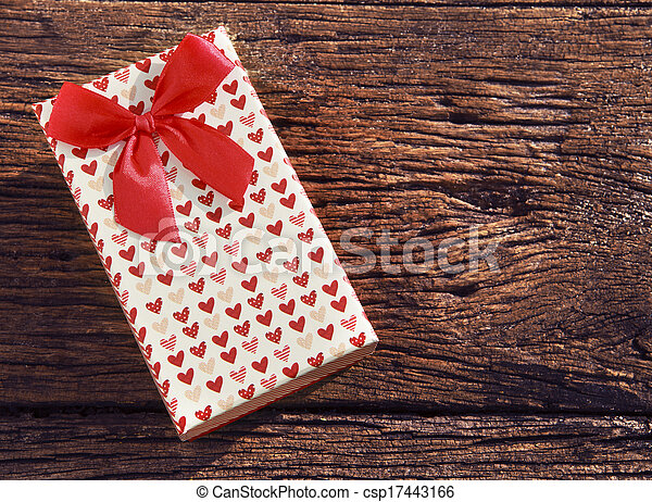 heart spot present gift box with red ribbon on old wood textured with copy space use for gift event in cristmas valentine and new years greeting - csp17443166