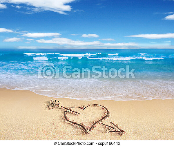 Heart with arrow, as love sign, drawn on the beach shore, with the see and sky in the background. - csp8166442
