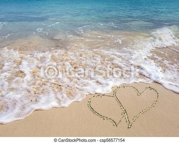 hearts in seashore sand with ocean surf - csp56577154