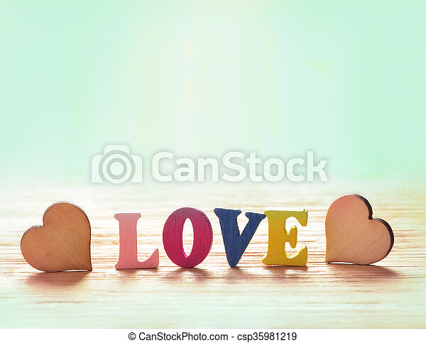 Hearts on wooden background with letters love - csp35981219