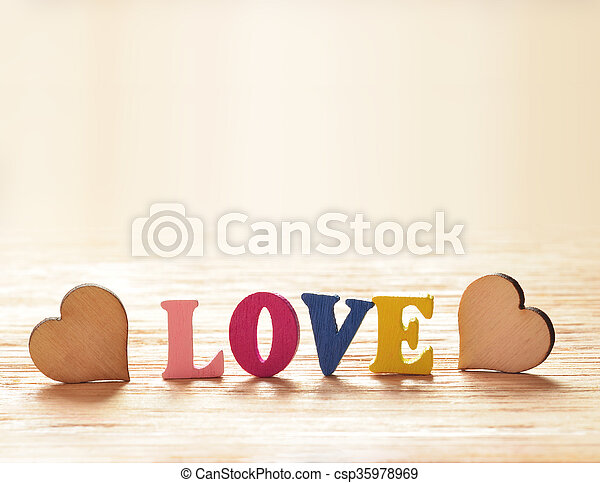 Hearts on wooden background with letters love - csp35978969