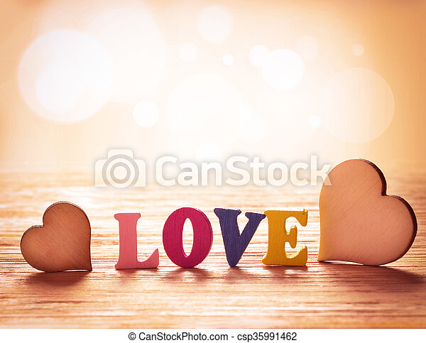 Hearts on wooden background with letters love - csp35991462