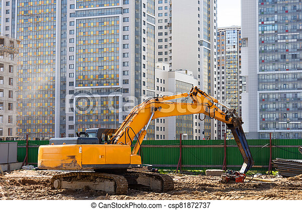 Heavy excavator in a working high frequency hydraulic vibratory mounted pile driver on road against the background of residential multi-storey buildings. - csp81872737