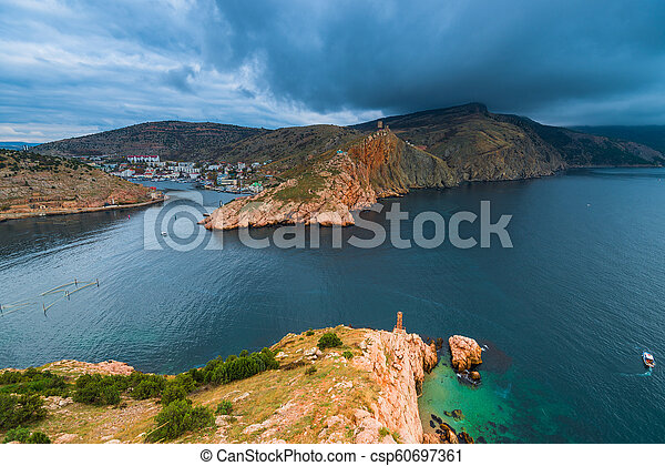 Heavy rain clouds over the bay, rocky mountains and city in the bay, seascape - csp60697361