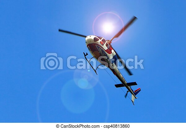 Helicopter flying under bright sun light and blue sky - csp40813860