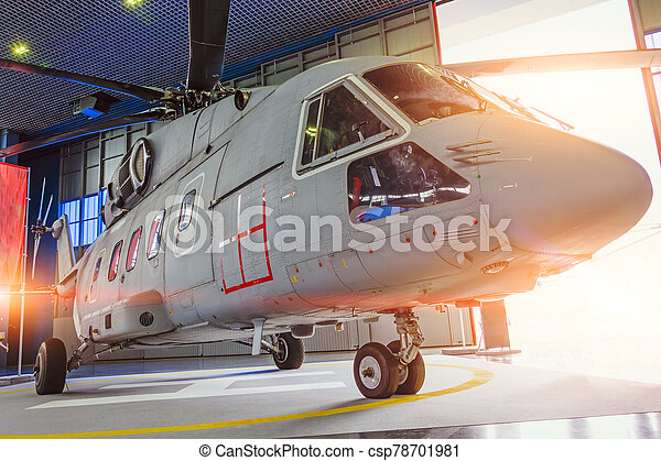 Helicopter in hangar with open gates for repair and production. - csp78701981