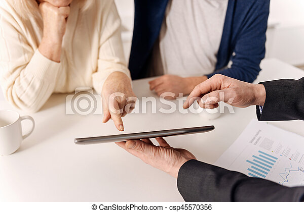 Helpful real estate agent working with aging couple of clients - csp45570356