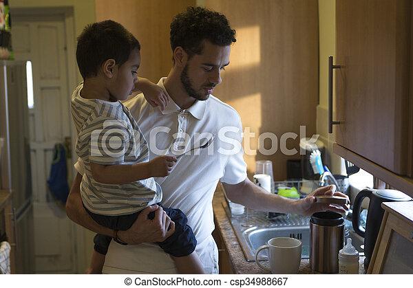 Helping daddy make tea - csp34988667