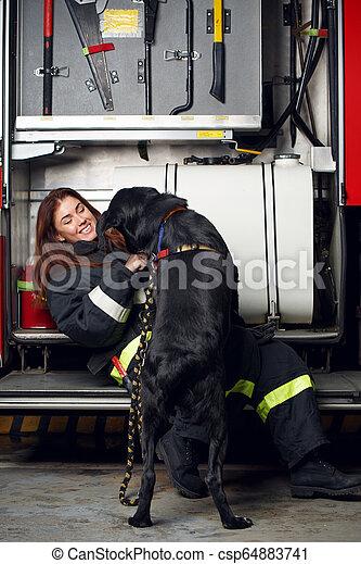 Foto de una bombero con perro negro sentado en el fondo del camión de bomberos en la estación - csp64883741