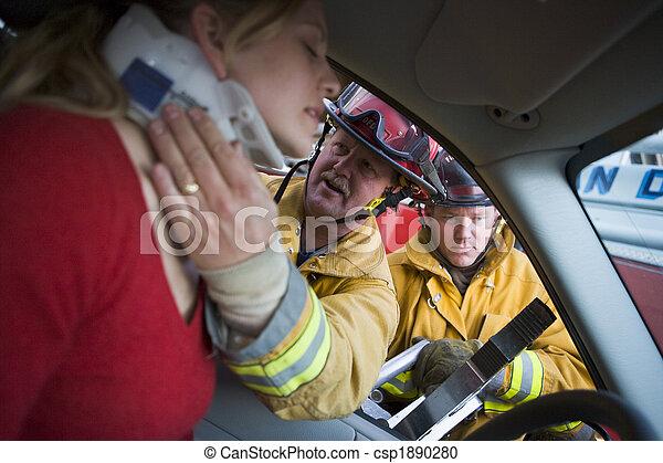 Bomberos ayudando a una mujer herida en un auto - csp1890280