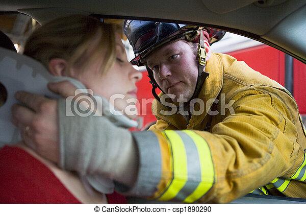 Bomberos ayudando a una mujer herida en un auto - csp1890290