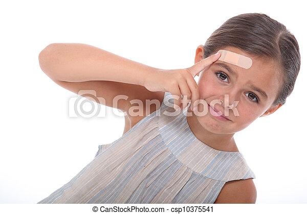 Una niña herida con un yeso en la frente - csp10375541