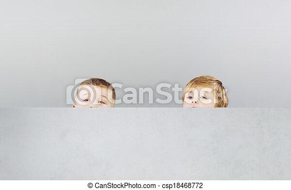 Dos hermanos escondiéndose durante el juego - csp18468772