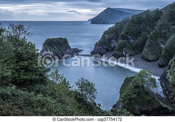 Hermosa imagen dramática del amanecer de una pequeña cueva aislada en Combe Martin Bay - csp37754172