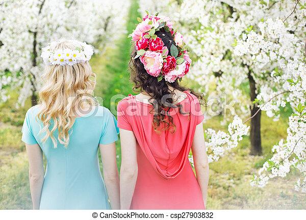 Dos hermosas mujeres caminando por el callejón de las flores - csp27903832