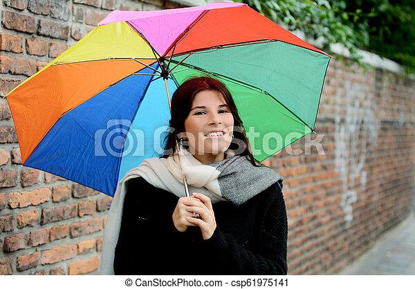 Hermosa mujer bajo un paraguas arcoíris - csp61975141