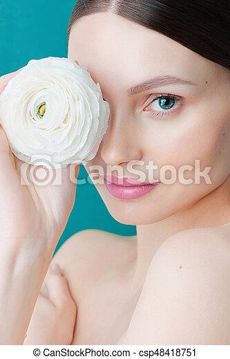 Retrato de una hermosa chica morena con una rosa blanca en un fondo azul - csp48418751