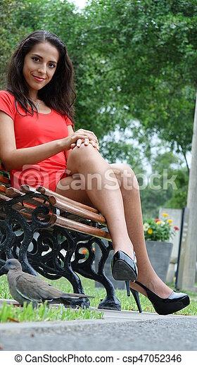 Hermosa mujer sentada en el banco del parque - csp47052346