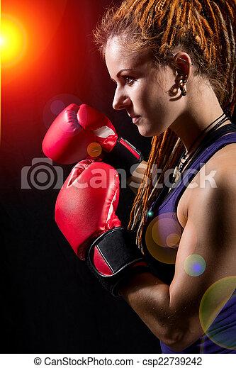 Hermosa chica con guantes de boxeo rojos, rastas en un bac negro - csp22739242