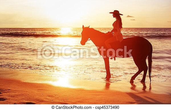 Hermosa mujer morena montando un caballo y viendo una puesta de sol - csp45373490