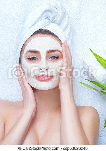 Mujer spa aplicando máscara de arcilla facial. Retrato de una hermosa chica con una toalla en la cabeza aplicando máscara facial - csp53626246