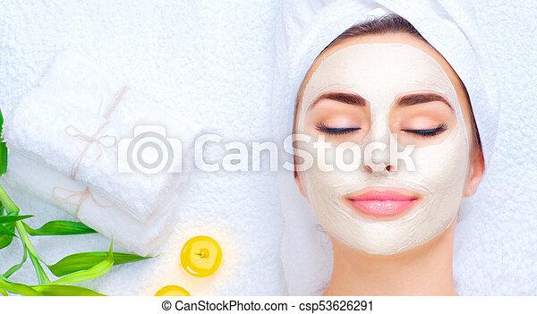 Mujer spa aplicando máscara facial. Retrato de una hermosa chica con una toalla en la cabeza aplicando una máscara de arcilla facial - csp53626291